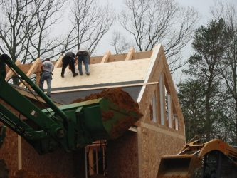 Workmen applying roof to new house