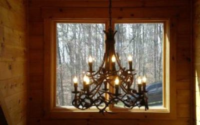 Antler light in a window of log home