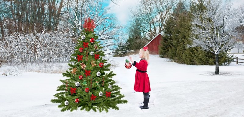 Young girl decorating a Christmas tree outdoors