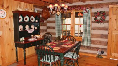 Green checked curtains in a cozy log home dining area