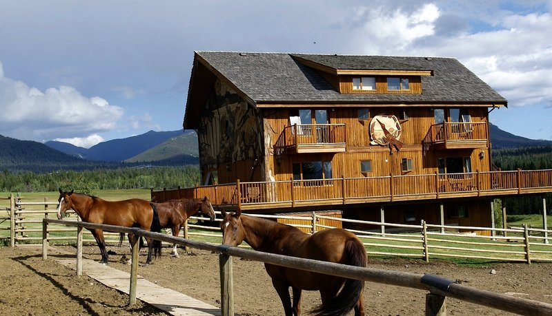 Timber frame barn with horses in the foreground