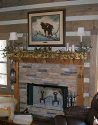 Fireplace mantle decorated with candles and greens