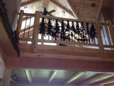Railing in log home with wrought iron forest scene
