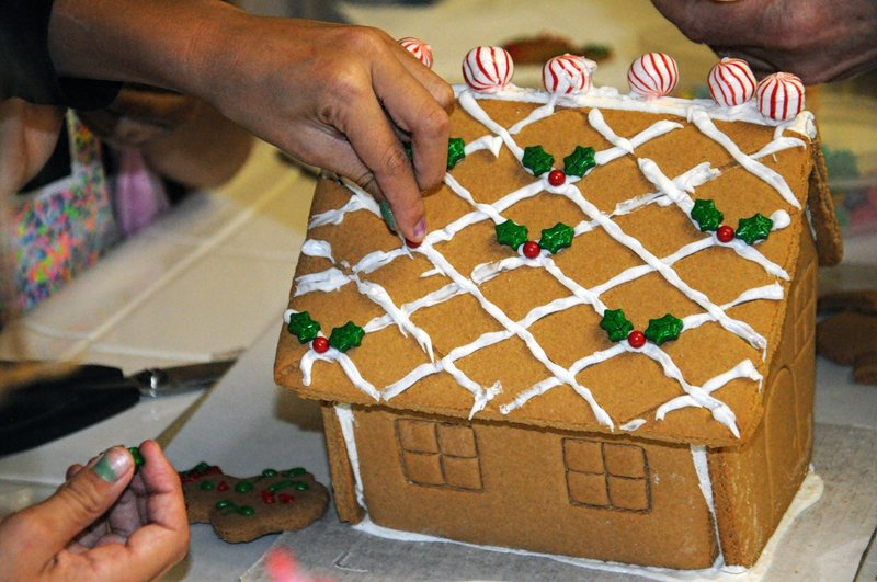 Woman decorating a gingerbread house