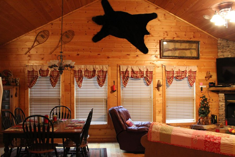 Red valance curtains in log cabin dining area