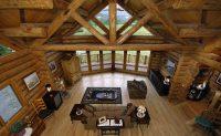 Rustic floor and huge log beams in log home great room