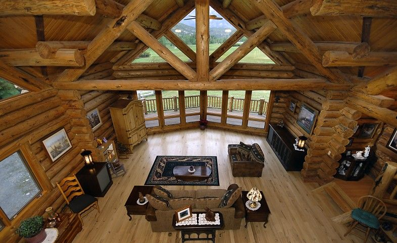 Rustic floor and huge log beams in log home great room