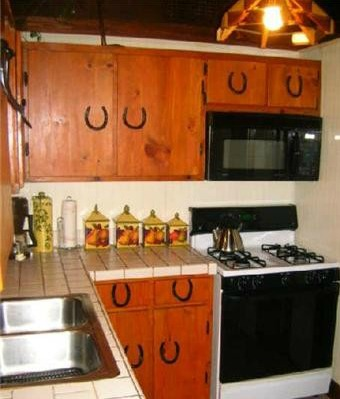 Horseshoes used as hardware on cabinets in log cabin kitchen
