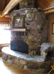Rustic stone fireplace with rounded corners