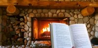 Rustic stone fireplace with fire and person reading