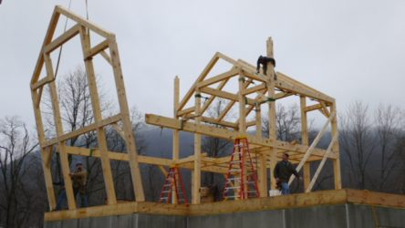 Timber frame sections being lifted into place by a crane
