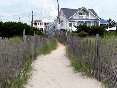 House by the ocean with a sandy path and fence