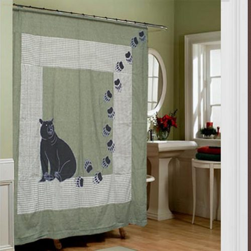 black bear sits on a small plaid green shower curtain with bear tracks