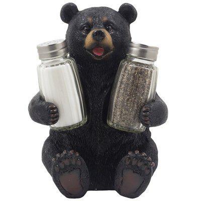 Cute black bear holding salt and pepper shakers