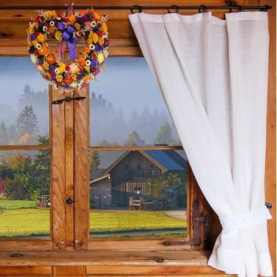 Window with white curtain and view of old barn