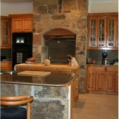 Rustic kitchen in log homes, with stone surround for stove