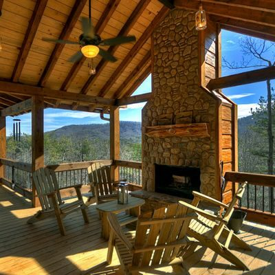 Adirondack chairs on porch in front of outdoor fireplace