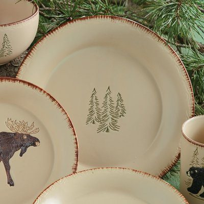 Cream colored dinnerware with moose or trees