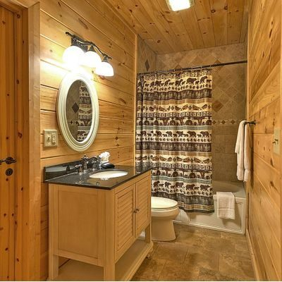 Log cabin bathroom with pretty shower curtain